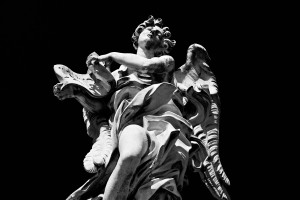 High-contrast monochrome shot of a statue on the River Tiber in Rome, Italy.