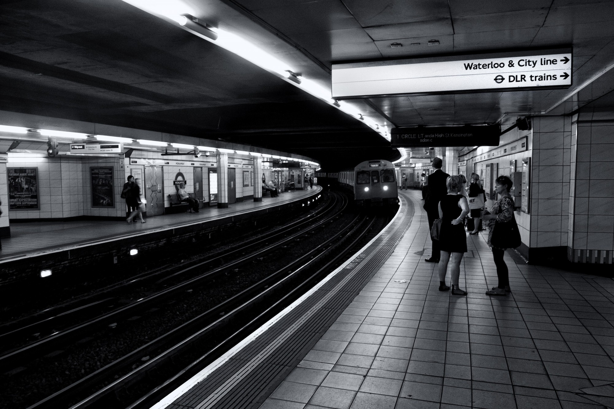 Monochrome shot of subway passengers as they wait for their train on the London Underground.